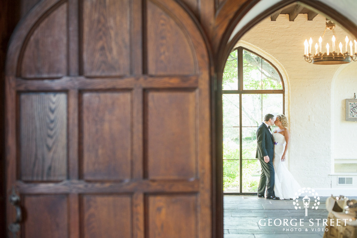 bride and groom kissing in sunny window archway
