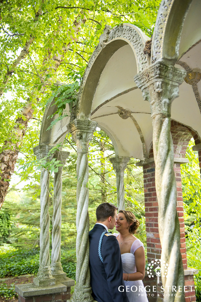 bride and groom smiling under stone archway in foresty area