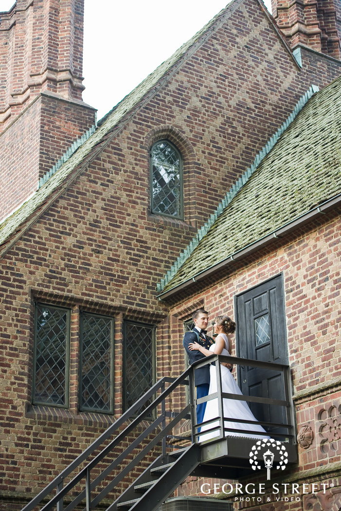 bride and groom standing on stairway outside of brick mansion