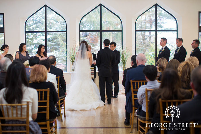 bride and groom standing together in indoor winter ceremony