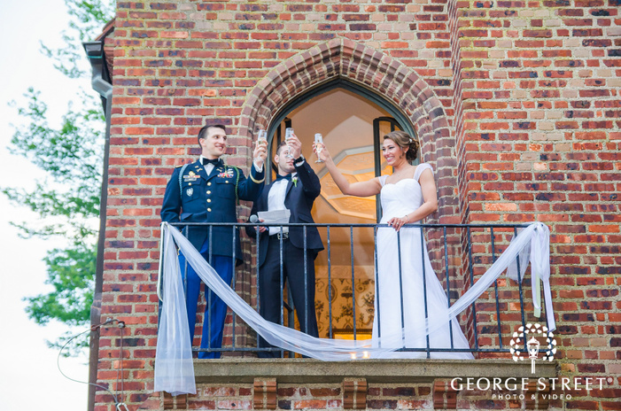 bride and groom toasting from balcony