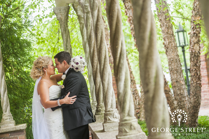 bride and groom touching noses under outdoor stone arches