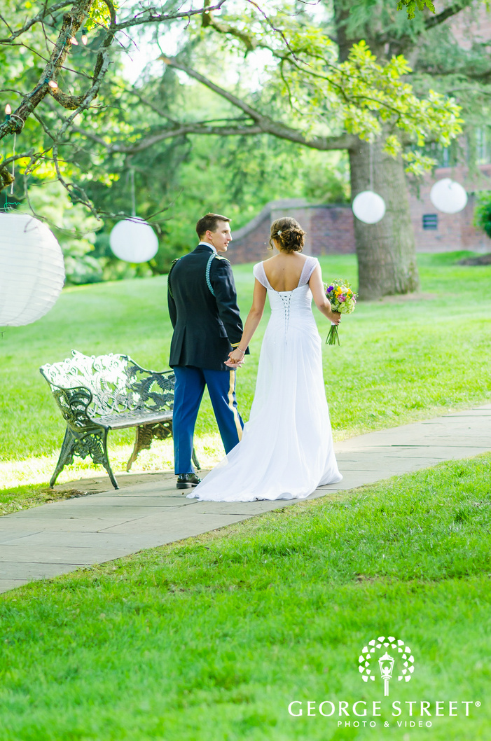 bride and groom walking through sunny outdoors with hanging paper lanterns