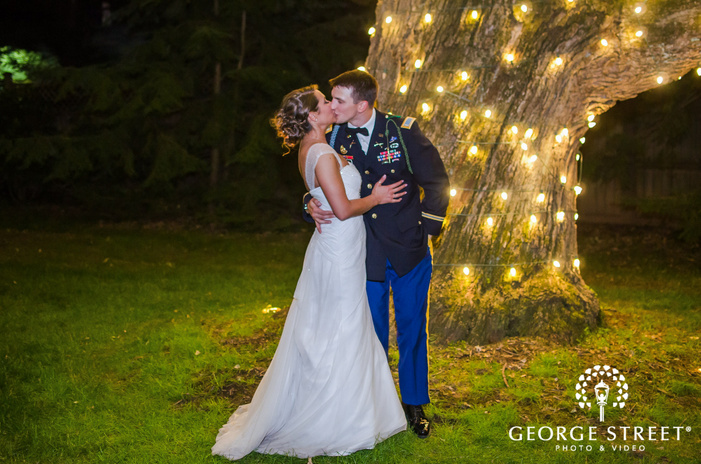 bride and military groom kissing under tree with lights at night