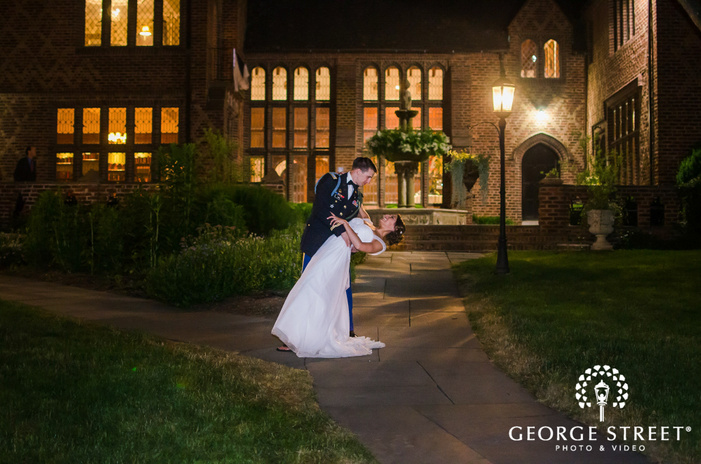 bride and military groom posing in courtyard under lantern at night