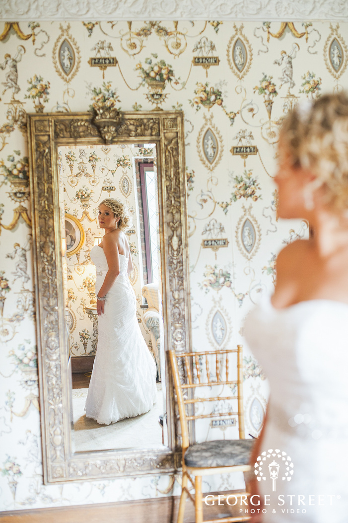bride looking at reflection in gold iron mirror in bright sunlit room