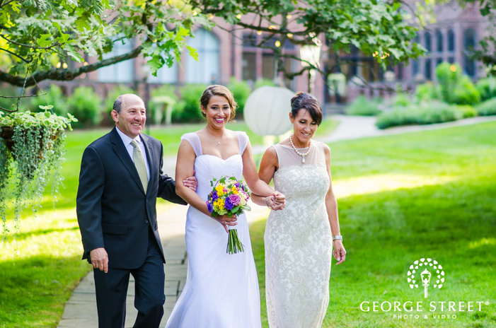 bride smiling walking with parents to outdoor sunny ceremony