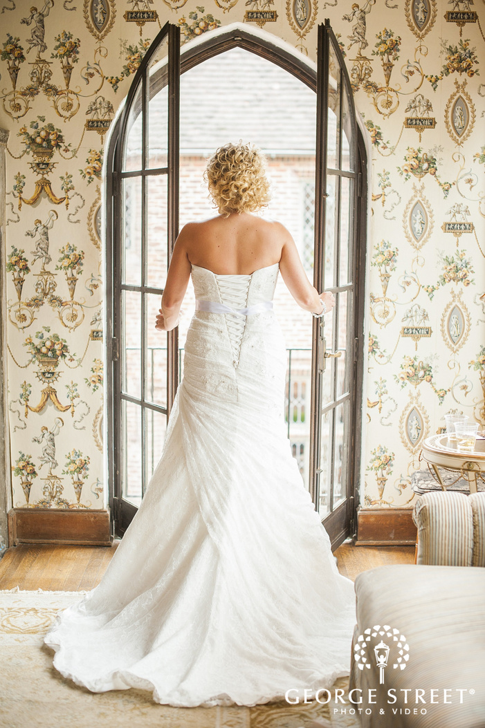 bride standing in sunny french doors