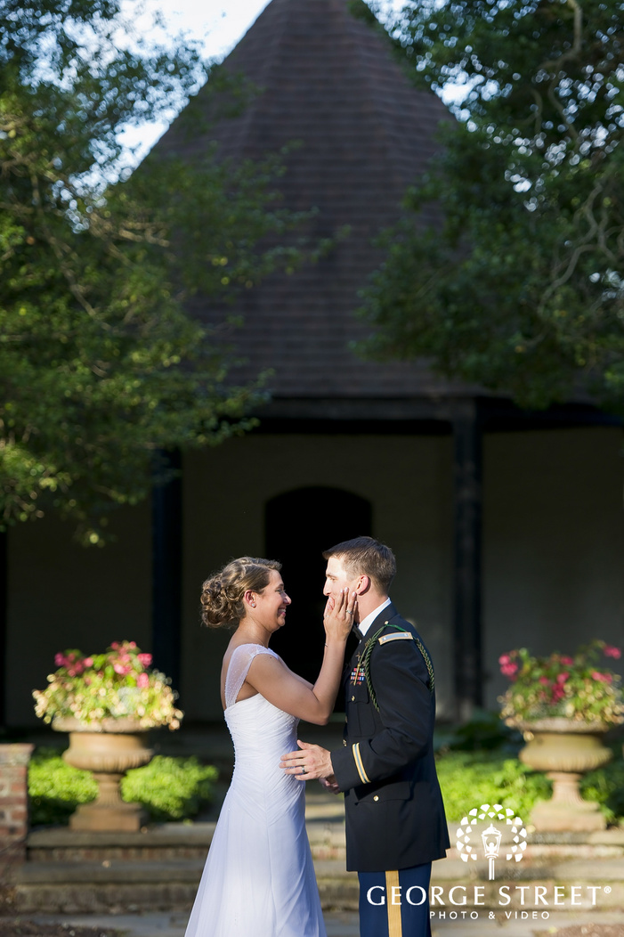 bride touching grooms cheeks in mansion courtyard