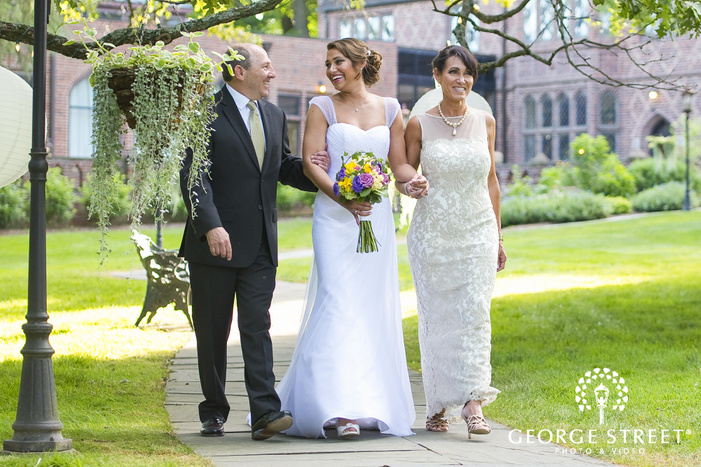 bride walking down the aisle with parents outside of mansion