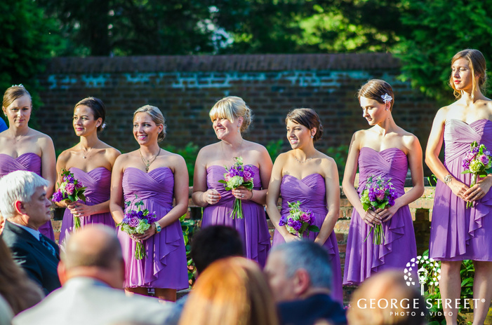 bridesmaids smiling in sunlight wearing short purple dresses