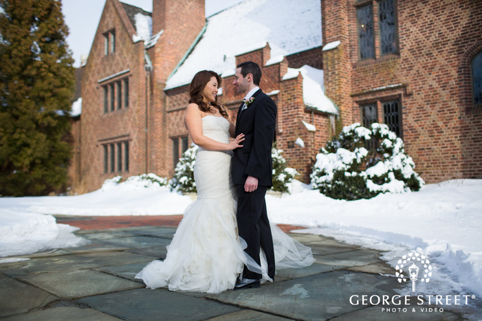 candid bride and groom posing in snowy courtyard