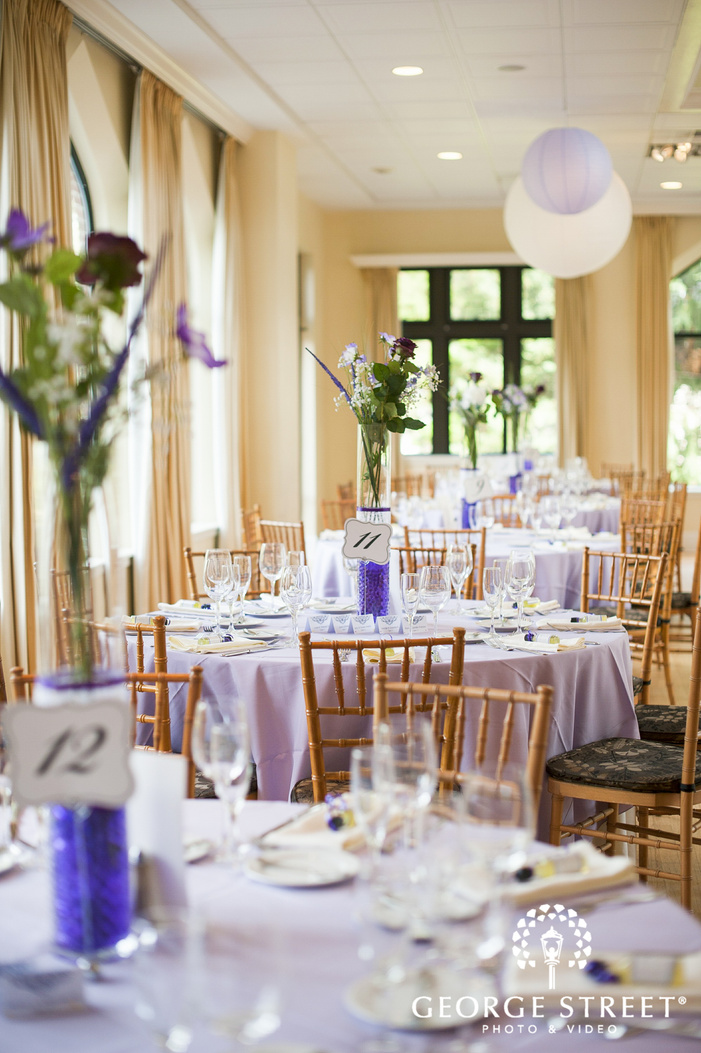 floral centerpieces on lilac purple recption tables by sunny windows