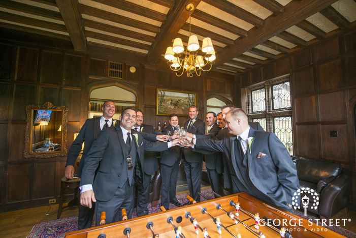 groom and groomsmen toasting in game room