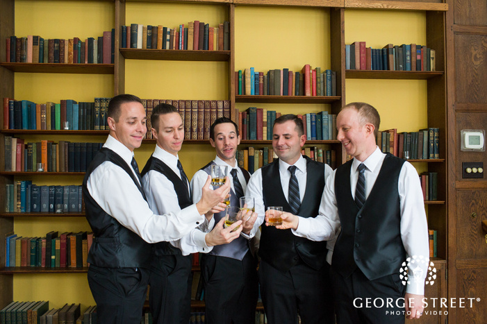 groom and groomsmen toasting whiskey in library room