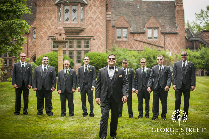 groom and groomsmen with sunglasses walking through open grass lawn