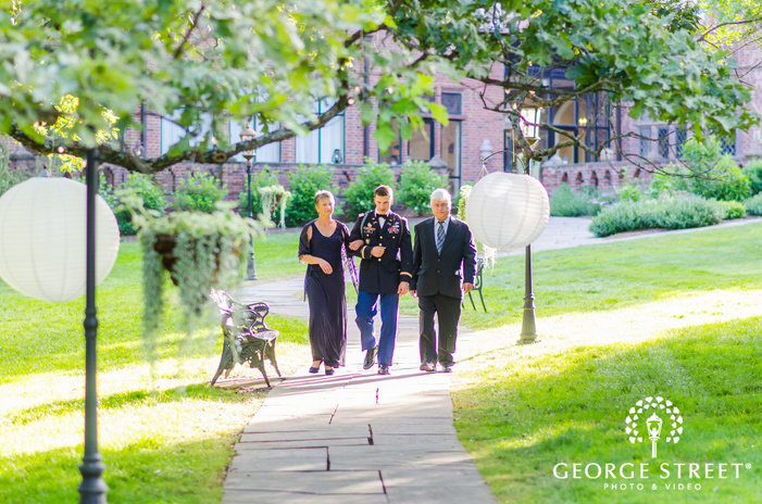 groom walking with parents to outdoor sunny ceremony