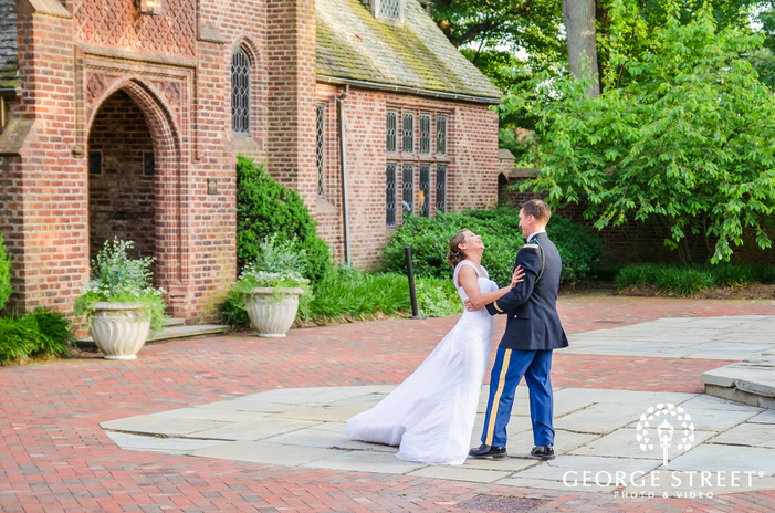 military groom and bride laughing in sunny open courtyard by mansion