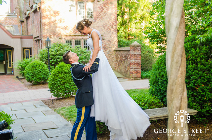 military groom lifting bride in sunny stone courtyard