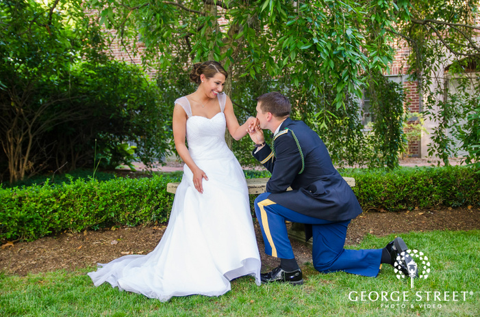military groom on one knee kissing brides hand in green outdoors