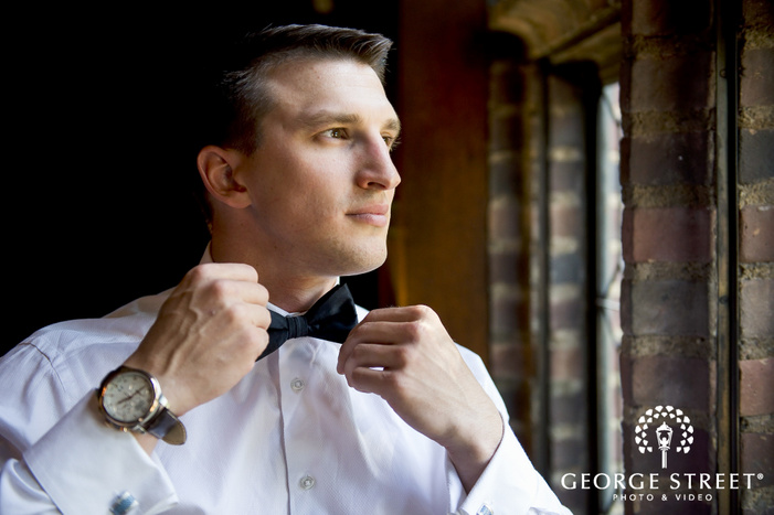 military groom tying bowtie near brick window