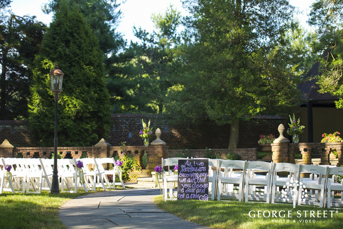 outdoor ceremony in courtyard with white chairs