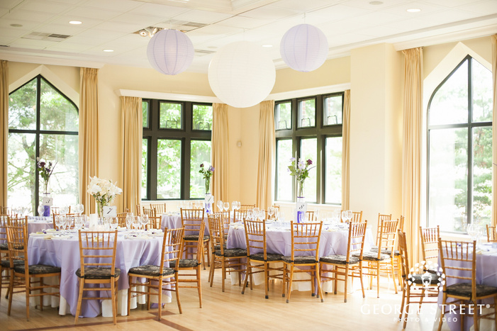 purple reception decor with hanging paper lanterns in gold room