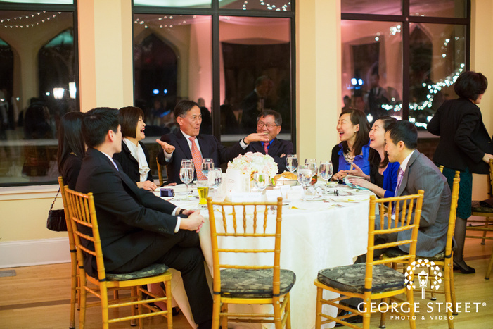 wedding guests laughing at reception table at night