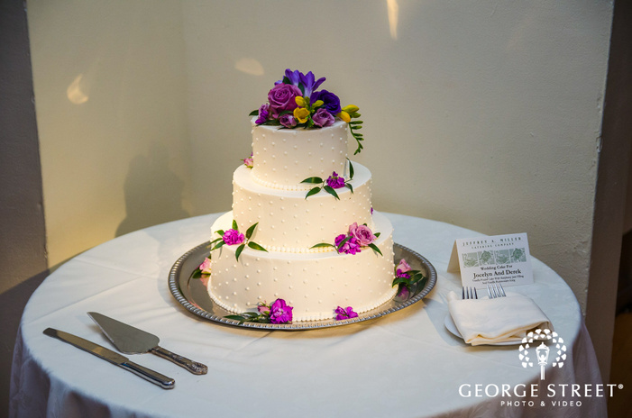 white tiered wedding cake with purple flowers