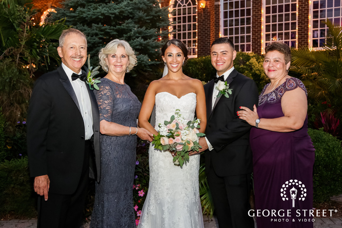blissful couple and parents at coral house wedding photo