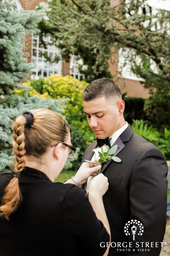 handsome groom puting on boutonniere wedding photo