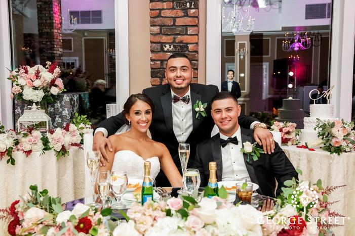 happy bride and groom with groomsman in reception wedding photo