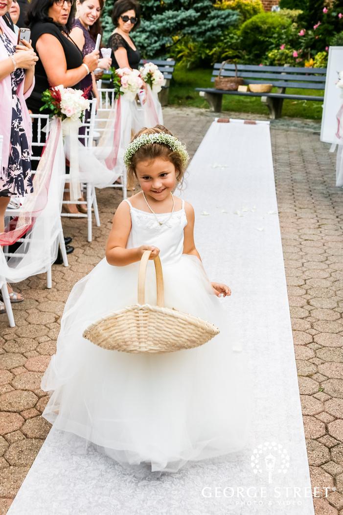 lovely flower girl walking towards wedding altar wedding photo