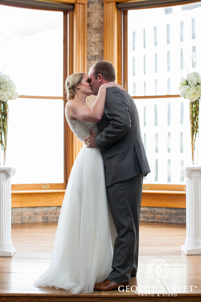 bride and groom first kiss at altar