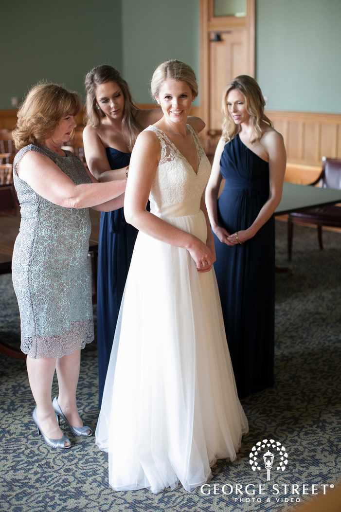 bridesmaids and mother helping bride into wedding dress