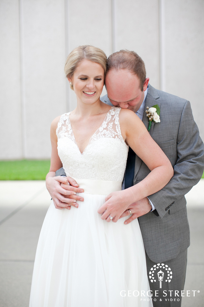 groom kissing brides shoulder airy outdoor portrait