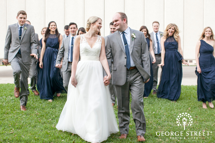 laughing bride and groom walking with wedding party