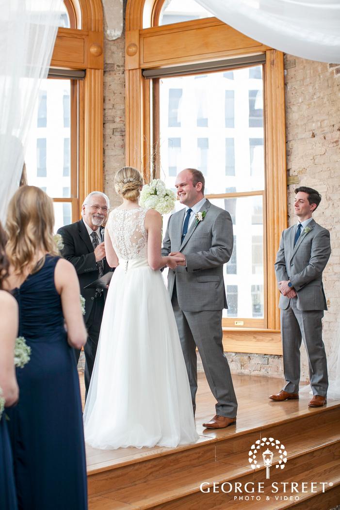 smiling groom looking at bride indoor wedding ceremony