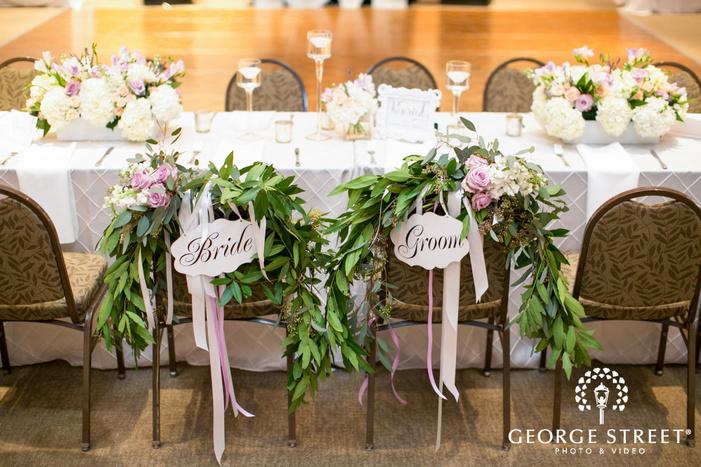 bride and groom leaf garland wedding chair details