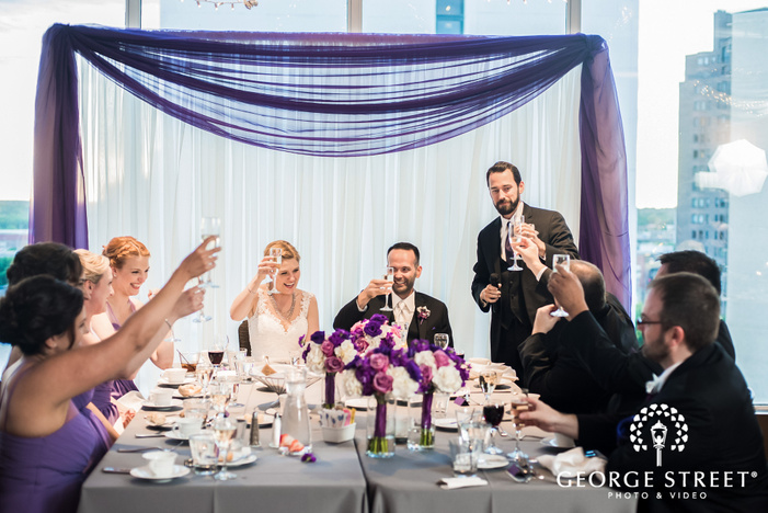 cheery bride and groom on reception table during reception toast wedding photo