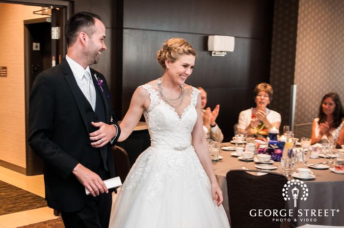 joyous bride ands groom reception hall entrance wedding photo