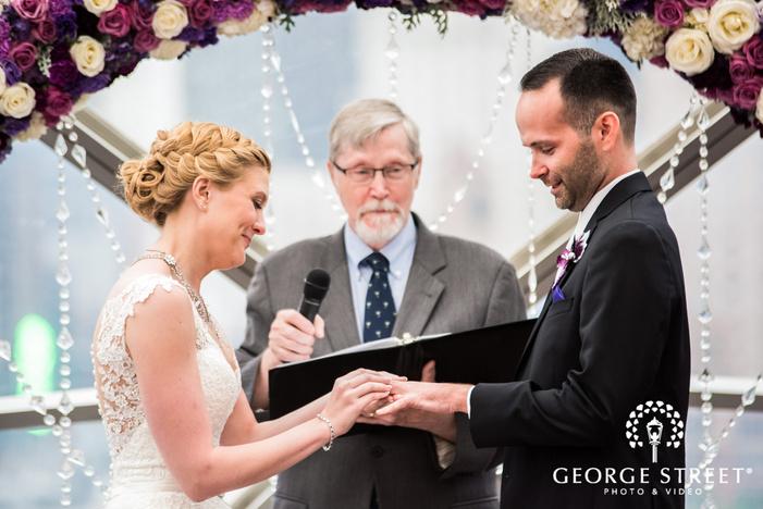 loving bride and groom ring exchange ceremony wedding photos