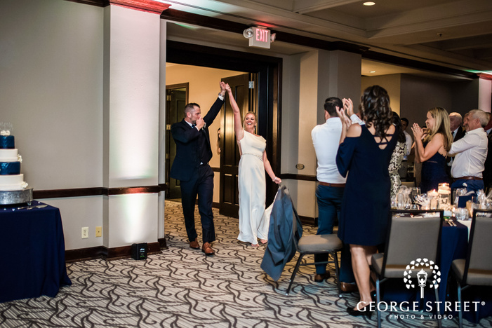 cheerful bride and groom reception entrance wedding photo