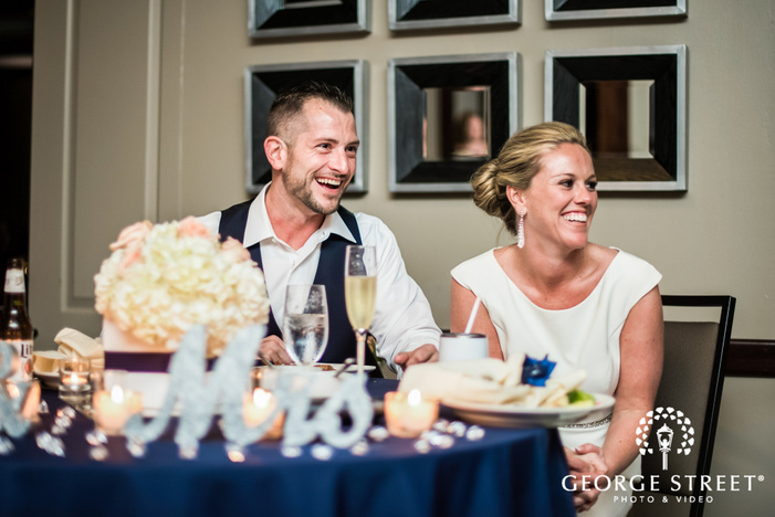 excited bride and groom on reception table wedding photography