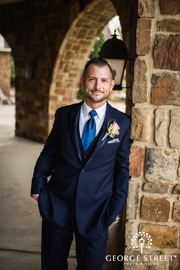 happy groom with stone wall wedding photo
