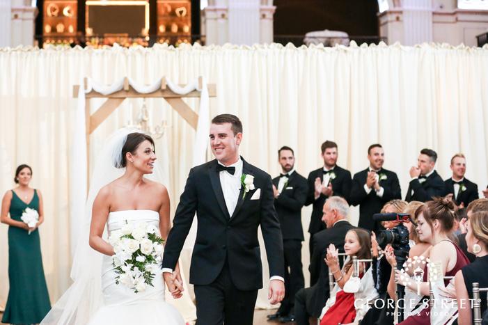 ballroom at the ben philadelphia indoor wedding ceremony bride and groom exit candid