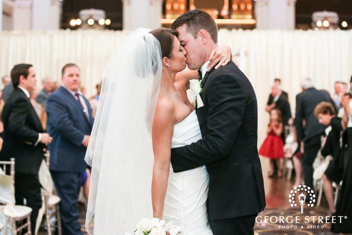 ballroom at the ben philadelphia indoor wedding ceremony bride and groom kiss exit candid