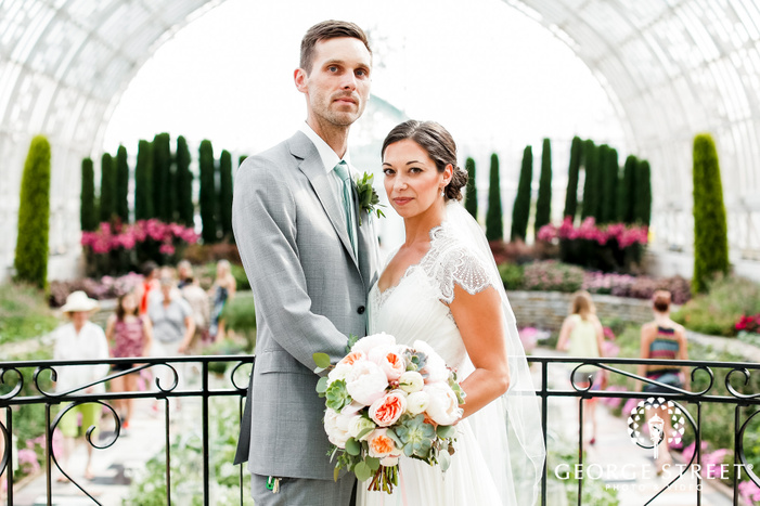 adorable bride and groom in garden glass house at como park zoo and conservatory in minneapolis