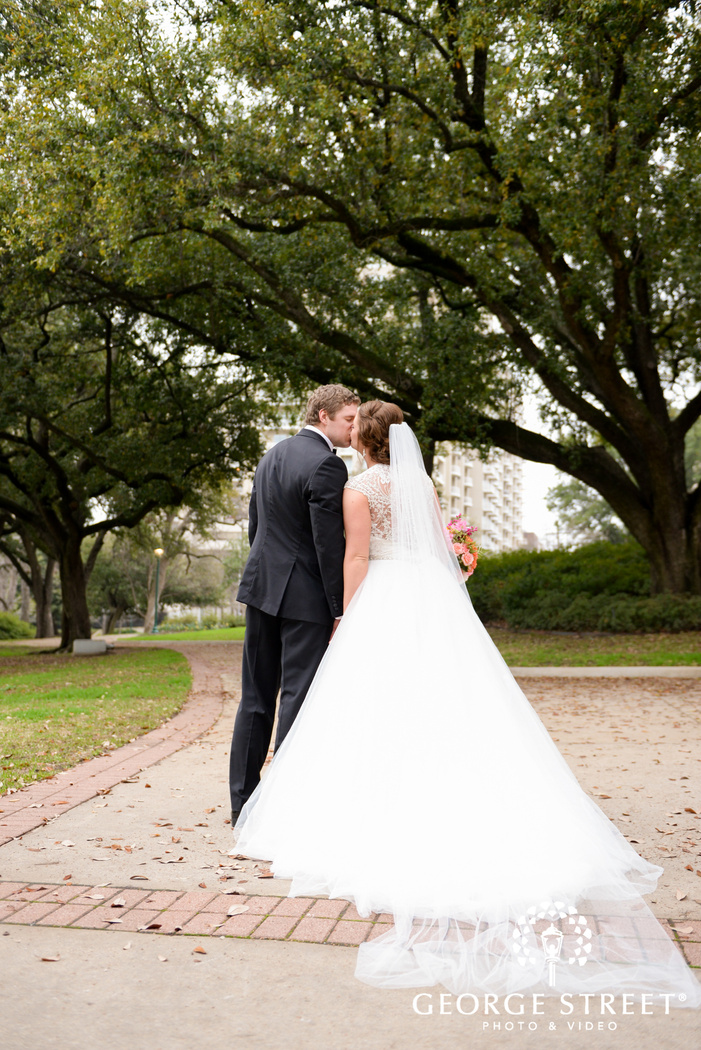 bride and groom kissing on path