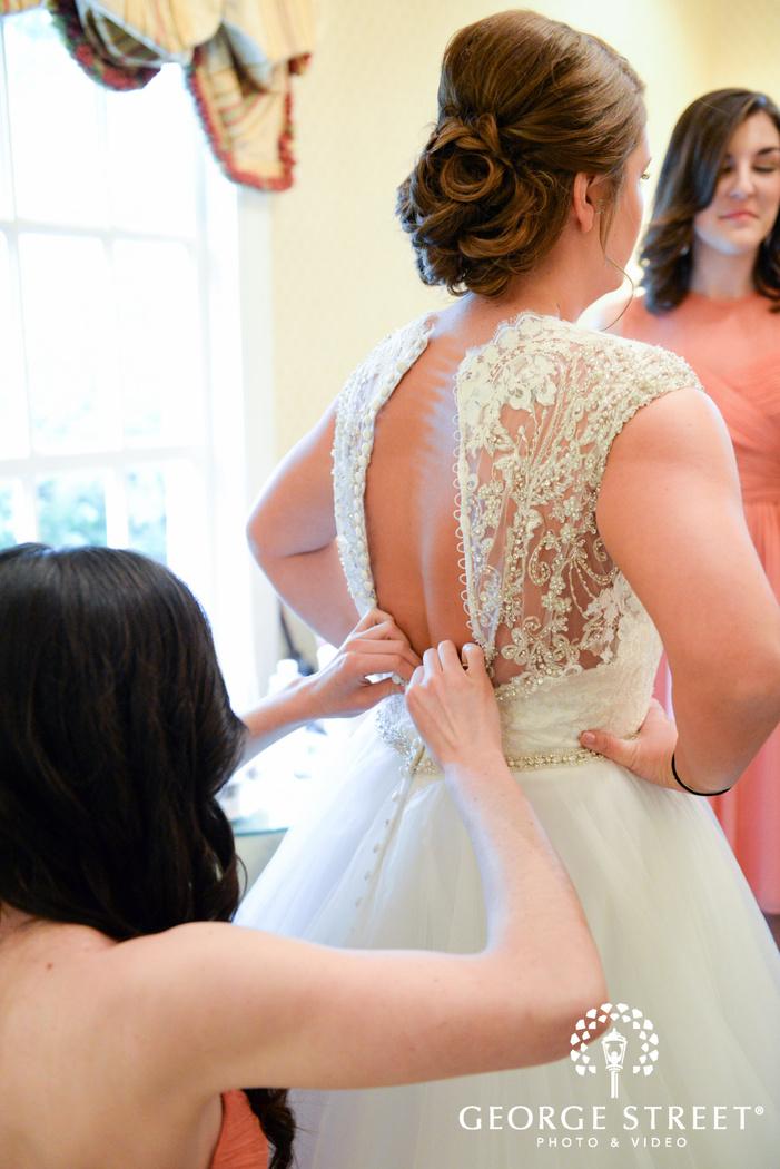 bridesmaid helping bride into wedding dress